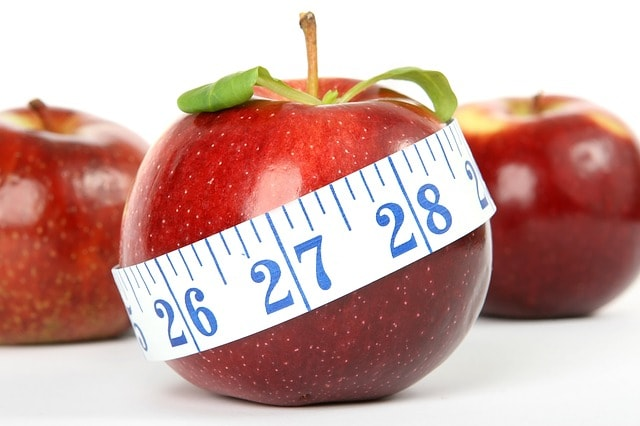 An apple wrapped into the measuring tape