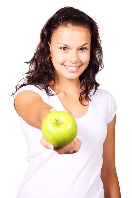 girl showing an apple in her hand